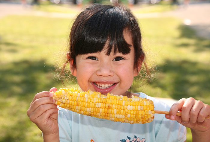 child eating corn on the cob